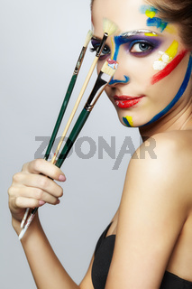Young female painter with  paint brush in hand  and  acrylic paint on face
