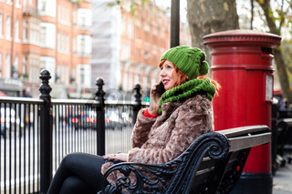 Young London lifestyle woman Talking on Mobile with red postbox on background