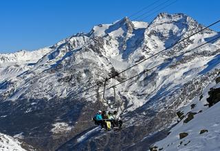 Skifahrer auf dem Längfluh Sesssellift vor Fletschhorn und Lagginhorn, Saas-Fee, Wallis, Schweiz