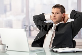 Young businessman relaxing in office