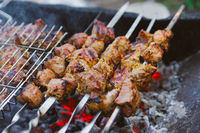 many roast meat pieces on skewer. shish kebab cooking process