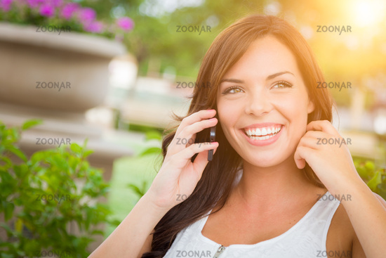 Young Adult Female Talking on Cell Phone Outdoors on Bench
