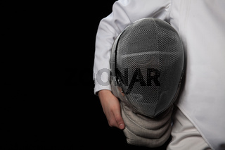 Fencer woman hold her helmet in hand wearing white fencing costume. Isolated on black background.