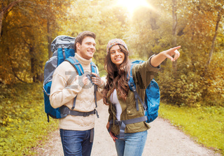 smiling couple with backpacks hiking