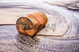 Old rusty barrel oil on beach