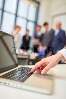 Mann drückt auf Tastatur eines Laptop