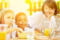 Kinder essen Müsli beim Frühstück im Ferienlager