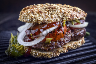 Barbecue Wagyu Hamburger with onions and tomatoes as close-up on a grillage