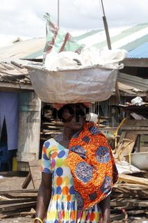 Ältere Frau transportiert Lasten auf dem Kopf