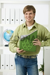 Young man holding green folder