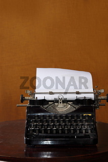 old typewriter with blank paper on a table