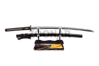Japanese sword and scabbard on stand  white background, black silk bag at front.