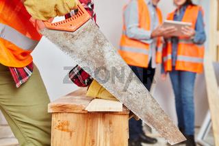 Handwerker sägt Holz mit Handsäge