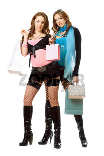 Two attractive young women after shopping. Isolated on white