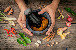 The Women hold pestle with mortar and spice red curry paste ingredient of thai popular food on rustic wooden background. Spices ingredients chilli ,pepper, garlic,galanga lemongrass and kaffir lime leaves .