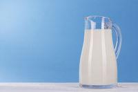Milch Krug aus Glas auf hell blau Hintergrund.