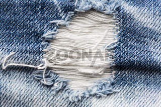 close up of hole on shabby denim or jeans clothes