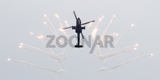 LEEUWARDEN, THE NETHERLANDS - JUN 11, 2016: Dutch AH-64 Apache attack helicopter firing off flares during the Royal Netherlands Air Force Days