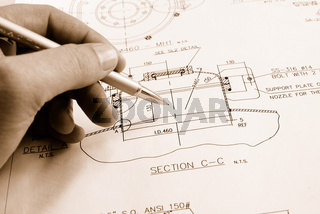 Hand of engineer drawing technical document.