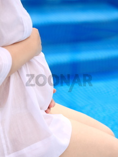 Pregnant woman near the swimming pool