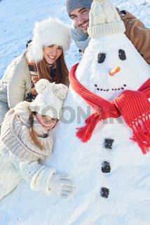 Kind baut mit den Eltern einen Schneemann