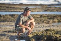 Man on rocks by ocean