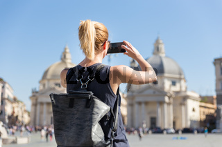 Female tourist with a fashinable vintage hipster backpack taking photo oof Piazza del Popolo in Rome, Italy by her mobile phone.