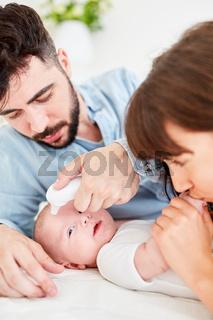 Eltern messen Fieber mit Stirnthermometer