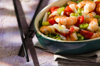 Close up of salad of shrimps and chopsticks