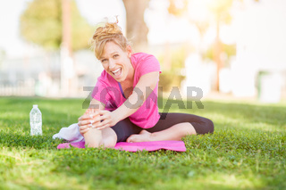 Young Fit Flexible Adult Woman Outdoors on The Grass With Yoga Mat Stretching Her Legs.