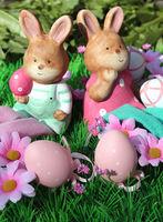 Zwei Osterhasen auf einer Blumenwiese mit bunten Eiern