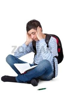 Junger Student lernt frustriert und müde auf Prüfung