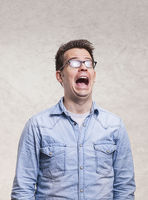 Portrait of a shocked, screaming, stunned or surprised young man -  isolated on light gray wall background