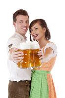 Junges verliebtes bayrisches Pärchen hält Masskrug zum Prosten.Freigestellt auf weissem Hintergrund.