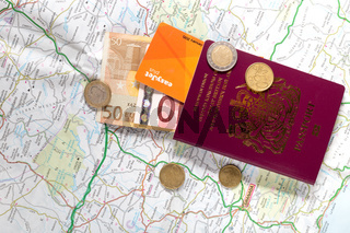 A British passport, Euro coins and notes on a road map of Spain, illustrating the concept of travel,