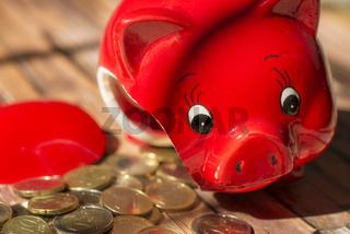 Zerbrochenes Sparschwein und Münzen