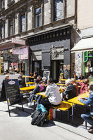 Some people enjoy a sunny day at the popular Viennese shopping street Neubaugasse