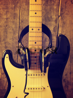 Vintage guitar with old studio headphones on wood