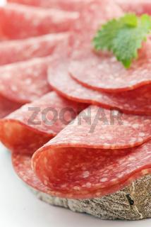 Spicy salami on farmhouse bread as closeup on a white plate