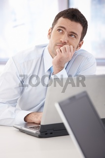Young businessman daydreaming at desk