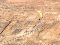 Aerial view of paraglider flying on sunny day