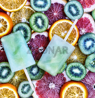 Concept: summer, heat, quenching thirst. Fruit ice, sliced fruit, kiwi, orange, grapefruit.