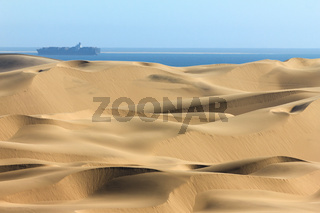 Big sand dunes. Ocean with ships and boat in background.
