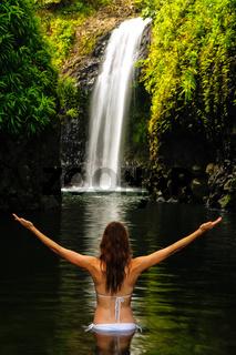 Young woman in bikini standing at Wainibau Waterfall on Taveuni Island, Fiji