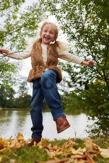 Mädchen hat Spaß und tanzt auf Blättern