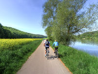 Two people cycling on a rural road in spring