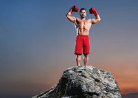 Muscular male boxer training outdoors