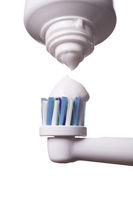 Close up of electric toothbrush and paste on white