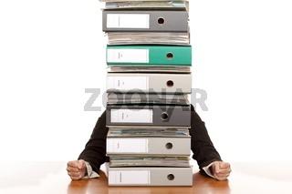 Geschäftsfrau sitzt hinter hohen Ordnerstapel und ist verzweifel