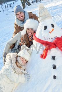 Glückliche Familie spielt mit dem Schneemann